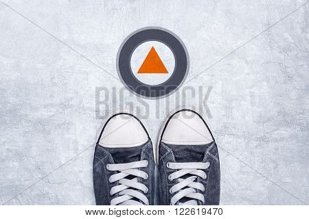 Young man in casual canvas shoes standing on concrete road modern direction arrow sign top view.