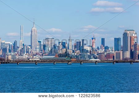JERSEY CITY NJ - MARCH 6: A view of Midtown Manhattan featuring the Empire State Building and 432 Park as seen from Liberty State Park on March 6 2016. The CNJRR terminal also at Liberty State Park is seen in the foreground.