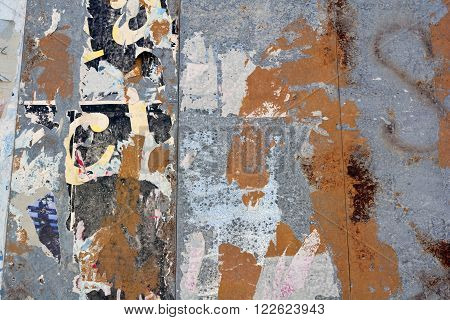 A metal billboard background with peeling posters and texture