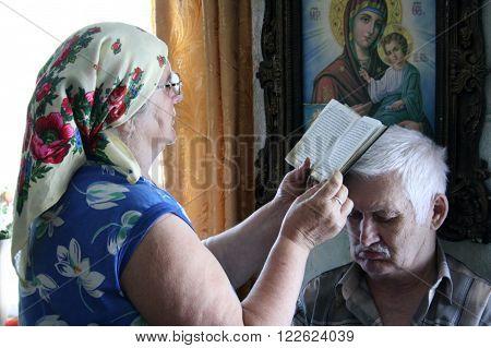 LUTSK UKRAINE - AUGUST 01 - Older woman read a prayer over the head of the patient man in Lutsk on August 01 2008.