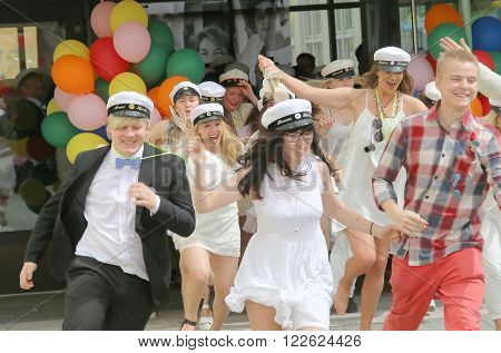STOCKHOLM SWEDEN - JUN 10 2015: Group of happy teenagers wearing graduation caps running out from school after graduation from high school at the school Globala gymnasiet June 10 2015 Stockholm Sweden
