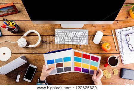 Designer at office desk working with color swatches. Smart watch on hand and smart phone on the table. Coffee cup, notepad and glasses and various office supplies around the workplace. Flat lay.