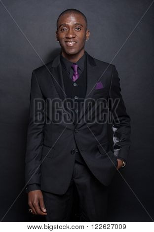 Studio fashion portrait of a handsome young African American businessman wearing a black suit and tie. Isolated on black background