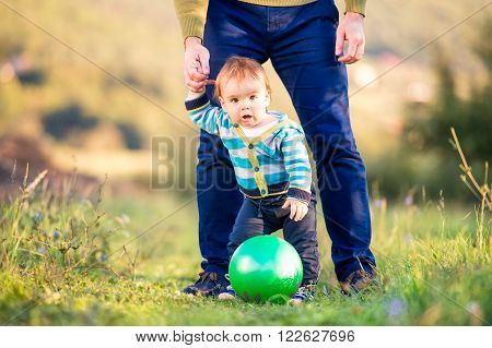 Unrecognizable father holding hands of his little son making first steps outside in green sunny nature, back view