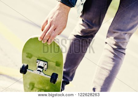 closeup of a young caucasian man skateboarding on a non-traffic street