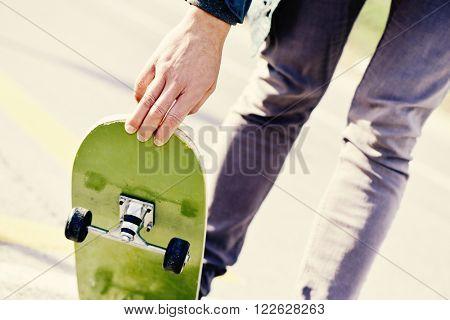 closeup of a young caucasian man skateboarding on a non-traffic street