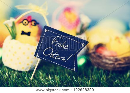 a funny teddy chick, emerging from a dot-patterned eggshell, with a black flag-shaped signboard with the text text Frohe Ostern, happy Easter in German, and some decorated eggs on the grass