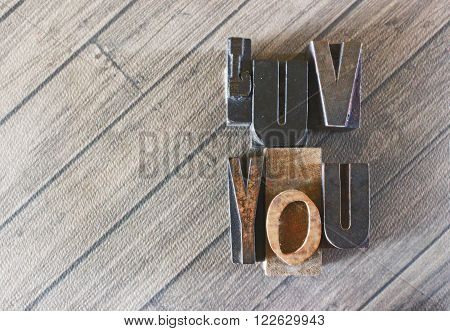 LUV YOU typeset wooden letters on a wood grain background
