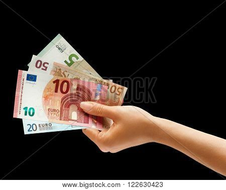 Hand holding euro money isolated on black background