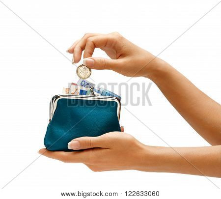 Womens hand throwing a coin one euro in the full purse on white background. Business concept