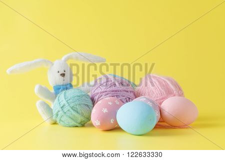 Colorful handmade easter eggs with wool clew and toy rabbit