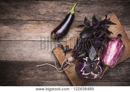 Tasty Aubergines And Basil On Chopping Board And Wooden Table