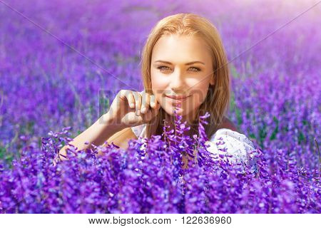 Portrait of beautiful blond woman sitting on fresh lavender field, enjoying gentle purple flowers, with pleasure spending sunny day in countryside