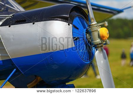 Engine and propeller of blue airplane. Close-up of a single-engine plane fuselage. Fragment of the aircraft.