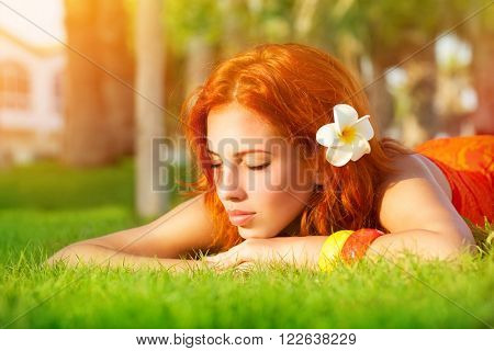 Portrait of cute calm girl lying down on fresh green grass with franjipani flower in red hair, dreamy closing eyes, enjoying day spa on luxury beach resort