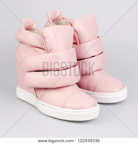 female pink boots in a grey background