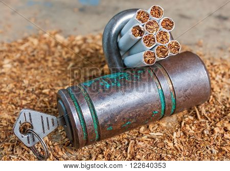 Antismoking background with broken cigarettes and a padlock. Quit smoking now