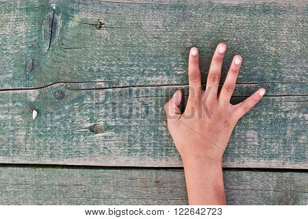 a hand tells us the right number one two three four five out of an aged wooden table