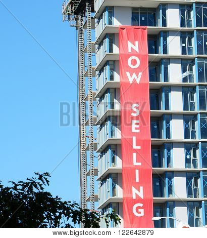 Real Estate Concrete Highrise Construction site, Now Selling Sign, blue sky background ** Note: Visible grain at 100%, best at smaller sizes