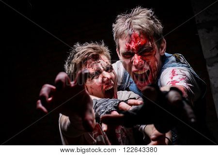 KIEV,UKRAINE - February 20 : People dressed as zombies look and pulled his hand into the camera during the quest game in zombie theme in Kiev,Ukraine on February 20,2016.