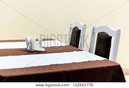 Generic view of restaurant table with table covered by tablecloth anf napkins on it empty table close up horizontal view