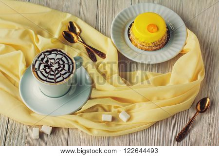 Mini Mousse Cakes Covered With Yellow Glaze And Coffee. Modern European Cake On Light Wooden Backgro