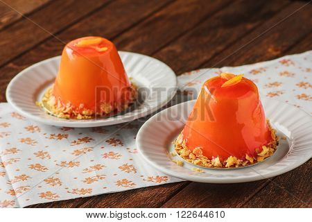 Mini Orande Mousse Cakes Covered With Glaze. Modern European Cake On Light Wooden Background