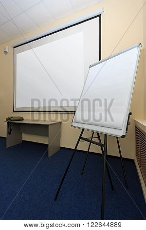 Generic view of blank screen of projector canvas and white board in office seminar meeting room