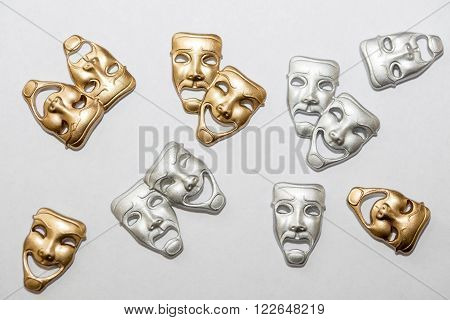 Small Greek drama masks in gold and silver on white background