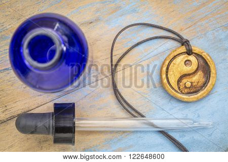 aromatherapy concept - essential oil diffuser ceramic pendant with yin and yang symbol, eye dropper and blue bottle