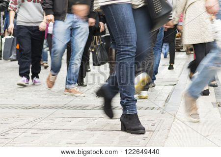 People walking in a pedestrian mall holding shopping bags