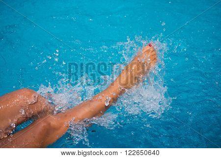 Female legs splashing water at the swimming pool