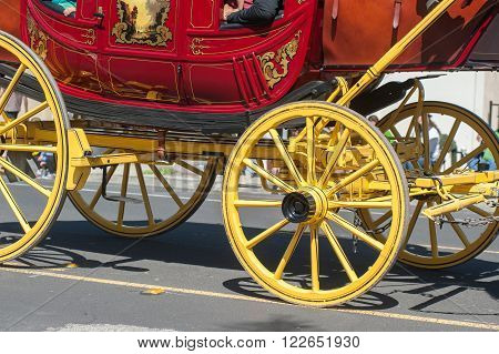 Shiny yellow and red Concord stagecoach on wheels.