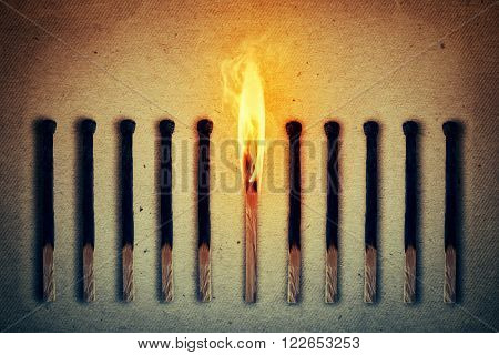 Burning match standing middle a row of extinguished burnt matches. Leadership concept