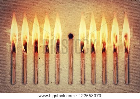 Whole unused match standing middle a row of burning matches. Standing out from the crowd leadership concept
