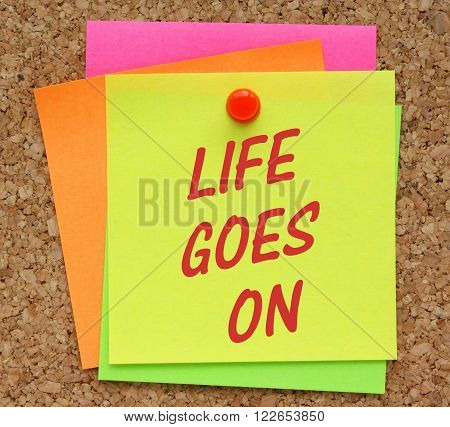 The message Life Goes On in red text on a yellow sticky note pinned to a cork notice board as a reminder