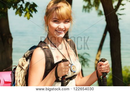 Young woman tourist hiking by sea ocean water. Backpacker on summer vacation trip journey. Girl with trekking poles sticks.