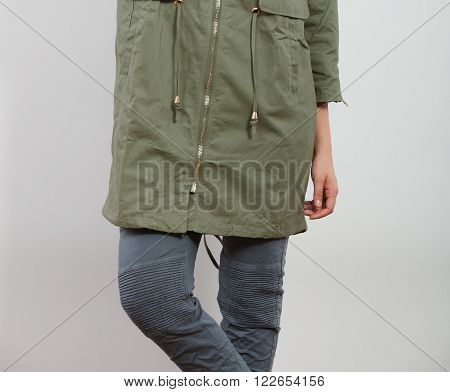Closeup of woman girl in dark green khaki coat and posing in studio. Winter autumn fall fashion.
