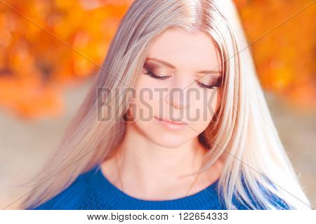 Beautiful blonde girl 20-24 year old posing outdoors over nature background closeup. Long hair. Sunny day. 20s.