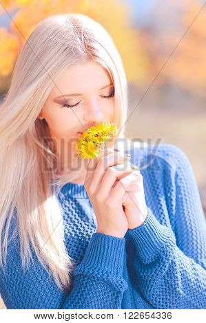 Beautiful blonde girl smelling dandelions outdoors over nature background. Eyes closed. Spring season. Sunny day. 20s.
