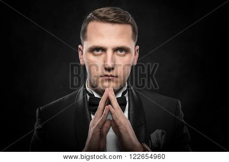 Portrait of businessman praying or thinking over dark background.