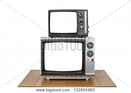 Vintage television stack on old wood table isolated on white with cut out screens.