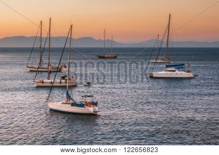 Sailboats at sunset in the Mediterranean Sea off the coast of Mandraki harbor. Rhodes Island. Greece