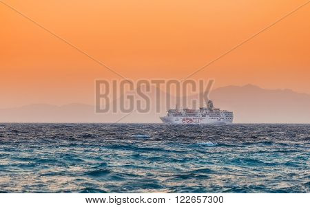 Greece, Rhodes - July 19 : Cruise ship goes lengthwise the coast at sunseton on July 19, 2014 in Rhodes, Greece