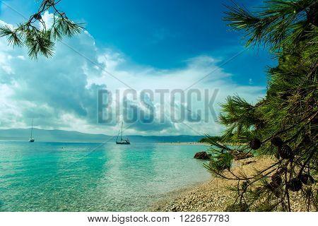 Beautiful seaview on island Brac in Croatia with yacht and rocky beach