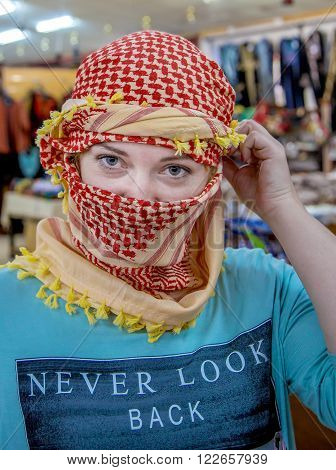 A girl of Slavic appearance wearing Arabic headdress. The girl looks at the camera close-up. Portrait