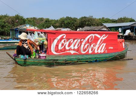 Tonle sap lake near Siem Reap, Cambodia, January 10, 2014: Coca Cola logo painted on wooden boat, floating village, Cambodia. Coca cola is probably the worlds most famous brand.