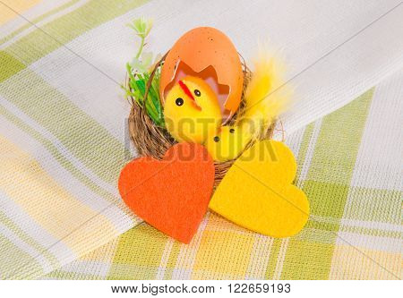 Easter decoration: hen with chicken in the nest and two colorful felt hearts on cotton napkin. Main colors: yellow white green orange.