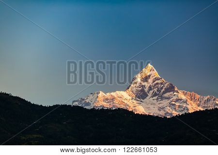 Mountain inspirational beautiful sunset landscape in Himalaya Mountains. Himalayas peak Machhapuchhare 6993m ASL over blue sunny sky Nepal