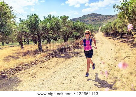 Trail runner woman cross country running on dirt road in mountains on summer beautiful day. Training and working out female jogging and exercising outdoors in nature, olive tree road on Crete, Greece